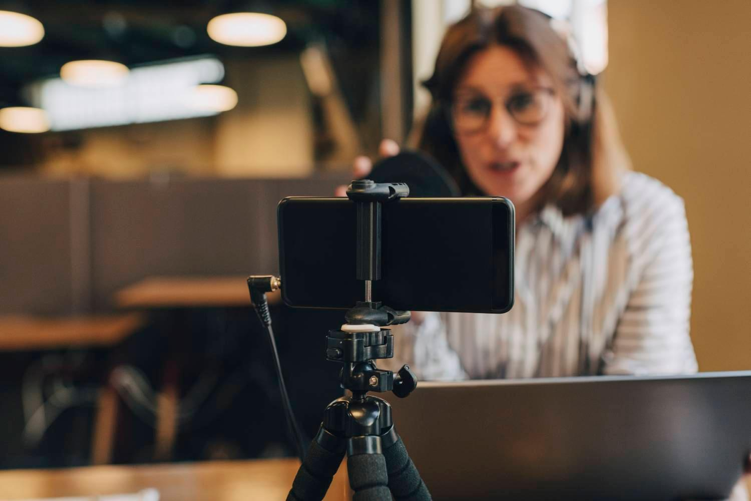 businesswoman-on-laptop-filming-on-phone