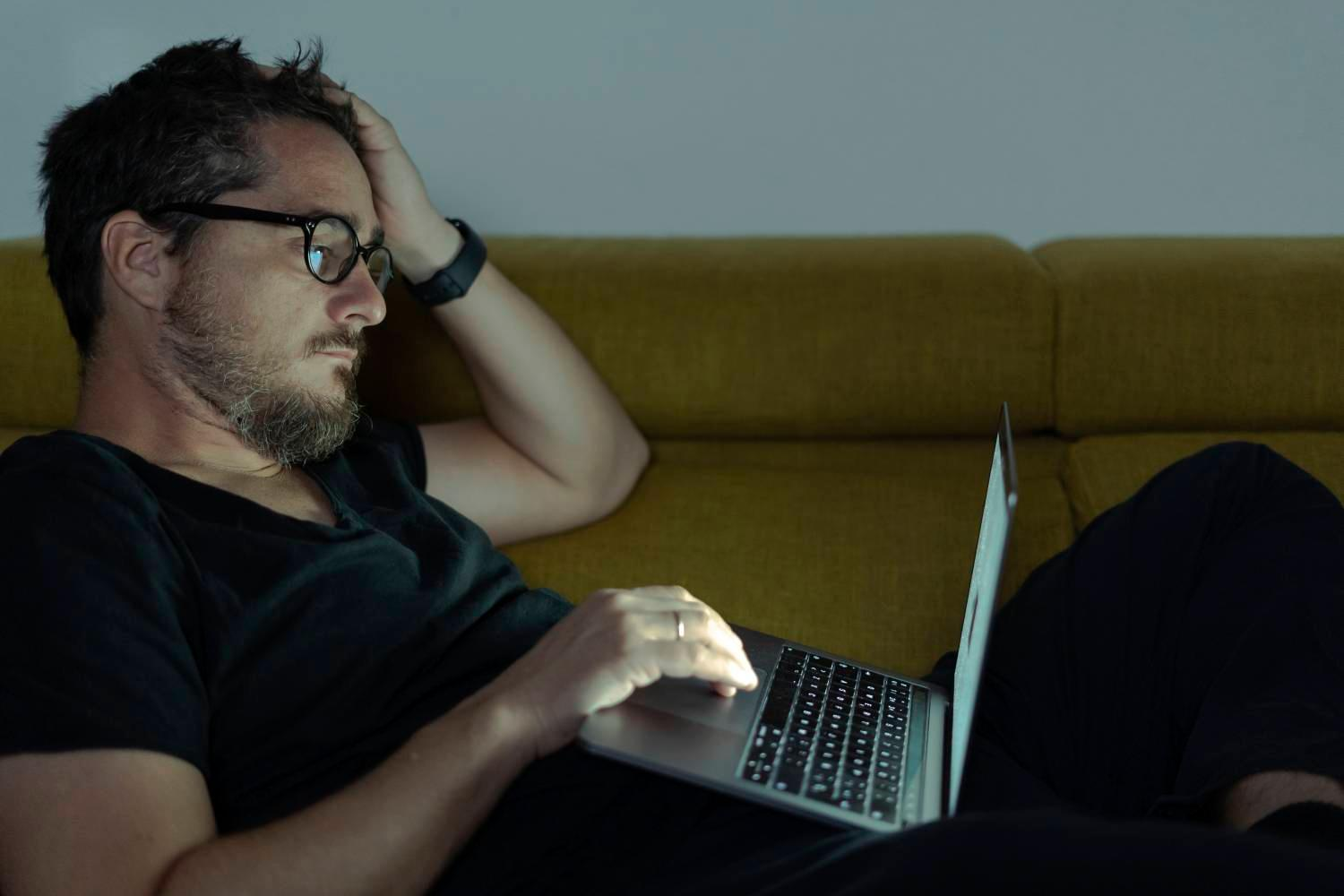 Getty image 1131380657, man lying on couch using laptop at night