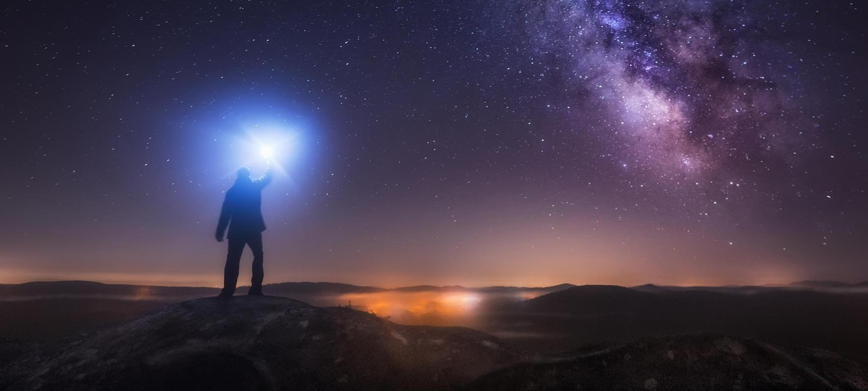600705680,Man Looking at Milky Way and lightning flash in night sky